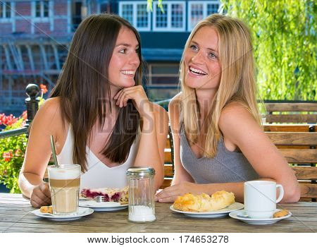 Two Girl Friends In Outdoor Cafe