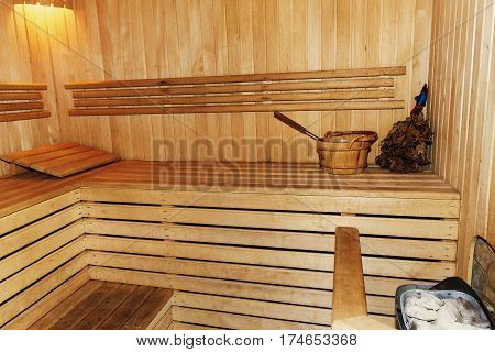Russian Wooden Sauna Room, Lumber Rustic Bench In Bath House, Wooden Bucket With Water And Birch Lea