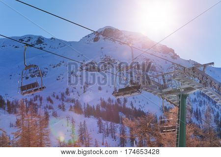 Beautiful mountain scene with empty chairlifts in the foreground at sunny day
