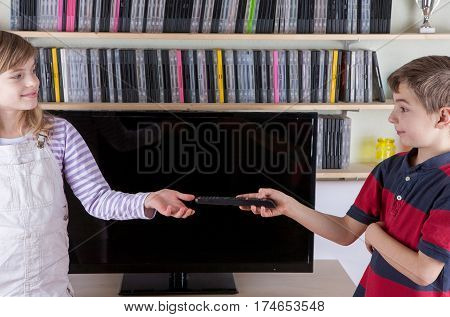 Young boy giving the remote control to his sister in front of the TV. Siblings finished fighting over the remote control.