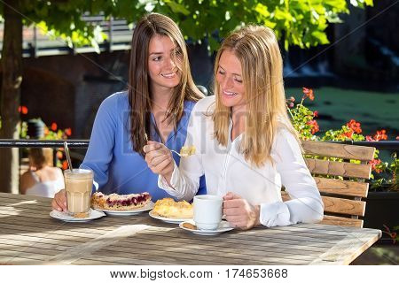 Young Woman Watching Her Friend Eating Cake