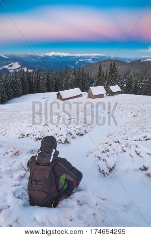 Hiker sits on a snow in a Carpathian mountain valley and contemplates the winter landscape.
