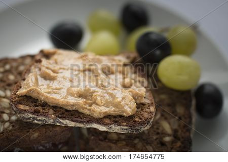 Peanut butter sandwich with green and dark grapes in background