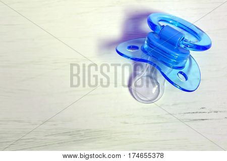 Blue baby soother on white grunge background
