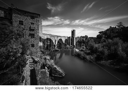 the Medieval Bridge is the emblem of Besalu, Spain, of an angular design with seven uneven arcs and two towers. The part of the town nearest to the bridge there are many narrow streets that belong to the ancient Jewish quarter