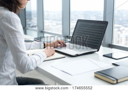 Office worker typing, working at her workplace, using laptop