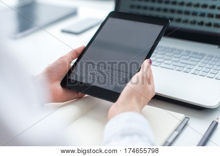Woman working with tablet pc and laptop computer on table.