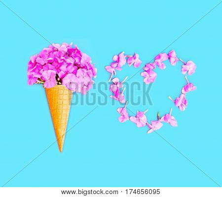 Ice Cream Cone With Flowers And Heart Shape Of Petals Over Blue Background Top View