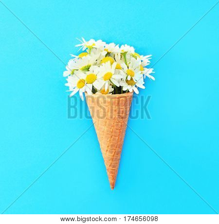 Ice Cream Cone With Chamomiles Flowers Over Blue Colorful Background Top View