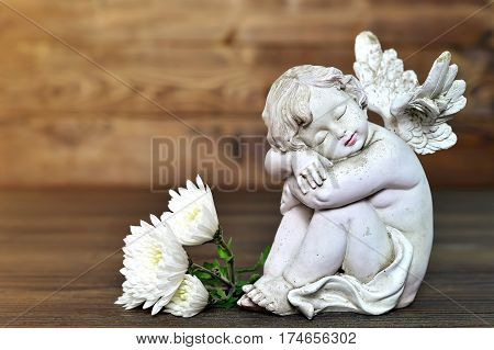 Little angel figurine and flowers on wooden background
