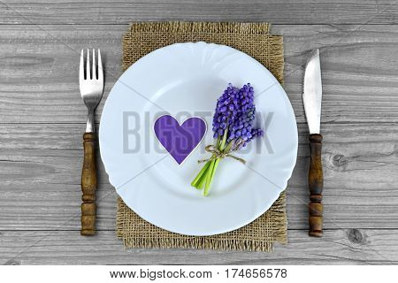 Mothers Day table setting: Plate and silverware on wooden background