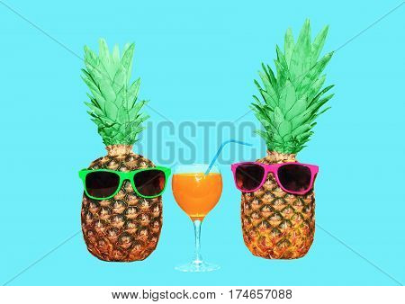 Two Pineapple With Sunglasses And Glass Fruit Juice On Blue Background, Colorful Ananas