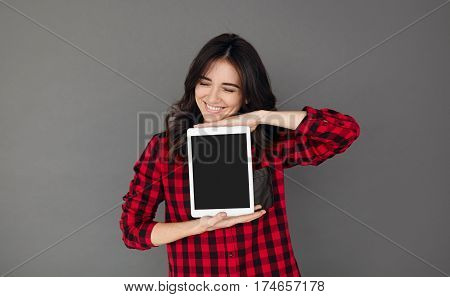 Portrait of a cheerful woman in red casual shirt showig blank tablet computer screen over gray background