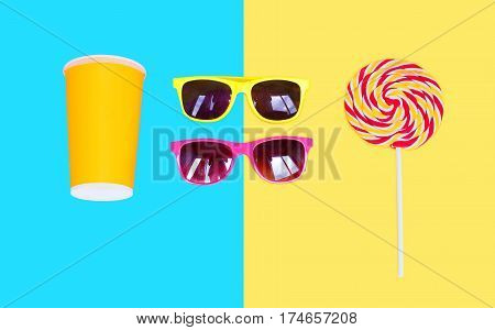 Two Sunglasses And Colorful Lollipop Caramel On Stick With Cup Juice Over Blue Yellow Background Top