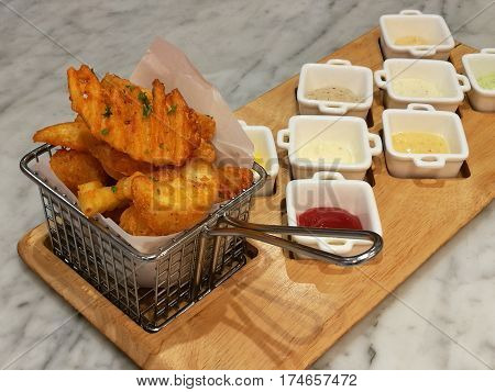 Golden French fries serving in the basket with 8 dipping sauces ketchup and mayo stylist food fusion food