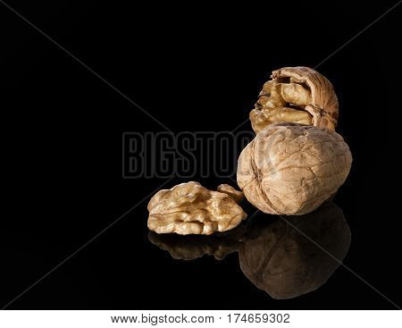 Many walnuts shelled and in-shell macro a reflection on a black background