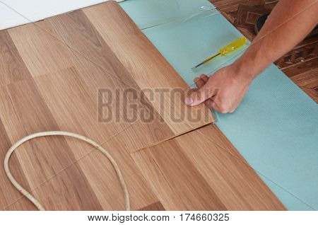 Man Installing New Laminate Wood Flooring. Installing wooden laminate flooring. Step by Step.