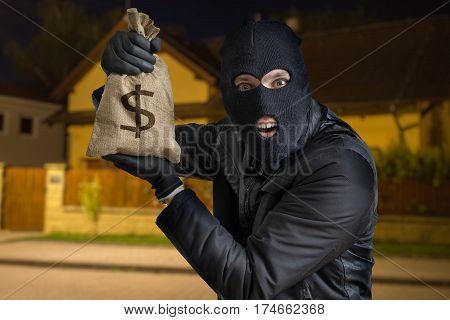 Happy robber or burglar is showing stolen bag full of money at night.