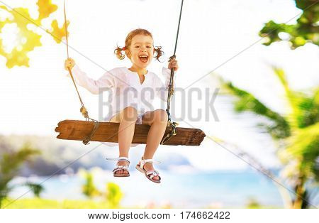 Happy child girl laughing and swinging on a swing at the beach near the ocean in summer