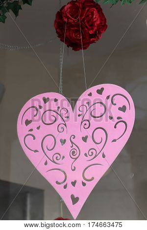 decorative pink felt heart hanging in a shop window