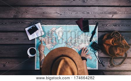 Tourist pointing at Alaska on the world map with her travel accessories around. Young woman wearing brown hat planning a tour looking at the world map.