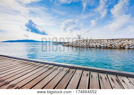 Wooden plank pier with seascape and bright blue sky for relax time at Khao Leam Ya National Park Rayong Province Thailand