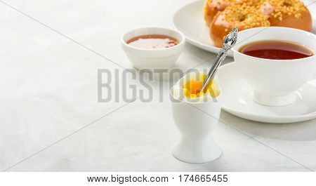 Delicious and healthy breakfast of boiled egg and brioche buns with black tea on a light background. Copy space soft focus .