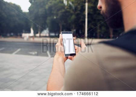 Phone with blank screen in hands, over the shoulder view. Shot with third-person view. Clipping path for screen.