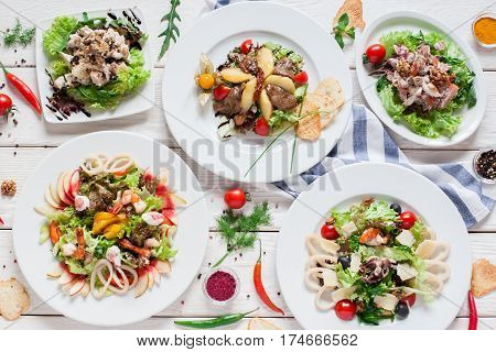 Warm salads assortment on restaurant table flat lay. Top view on buffet with variety of meat side dishes. Menu, banquet, food set, party concept