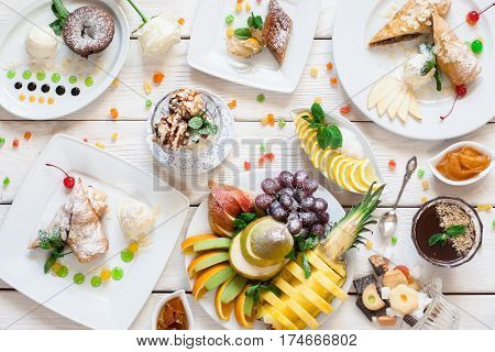 Sweet desserts with fruit assortment flat lay. Top view on variety of cakes, fresh fruits and sweets. Buffet, party, birthday, childhood concept