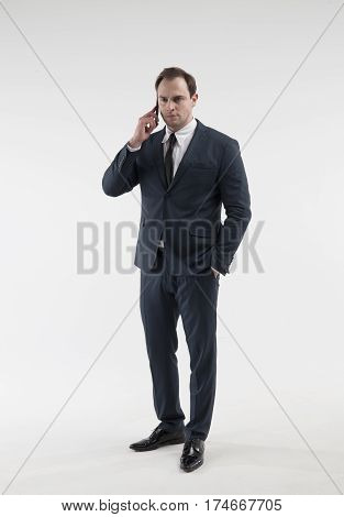 Portrait of a mature businessman with smartphone in a suit on white background