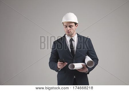 Portrait of a engineer businessman in white helmet and in a stylish suit on gray background