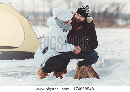 happy couple in warm clothes at winter picnic. bearded boy hold girls hads. concept of the, winter camping, hiking, extream recreation, tourism