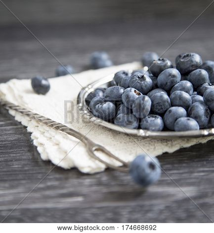 Blueberry in a plate on a wooden background