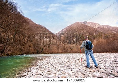 Hiker on the bank of a river. Trekking toward mountain. Rambler about 60 years old.