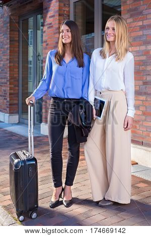 Two Young Women Standing With Suitcase