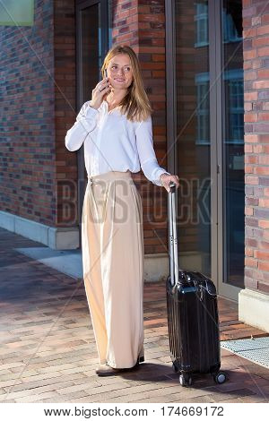 Full length portrait of beautiful blonde woman in white blouse with black suitcase on wheels talking by the phone standing outside near bricked building entrance smiling and looking away