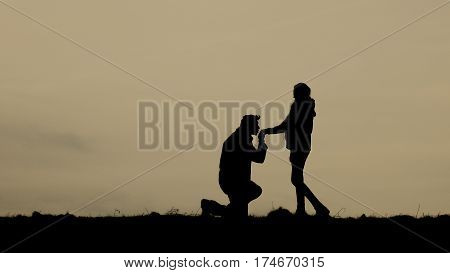 Silhouette of two people during sundown on the horizont.  Two loving young people. Kneeling boy before girl. He is kissing her hand.