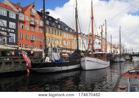 COPENHAGEN, DENMARK - JUNE 29, 2016: Old ships are located along the harbor of Nyhavn to complement the colorfulness of this showplace.