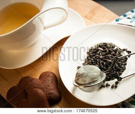 green tea leaves next to a cup of tea served with chocolate cookies
