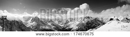 Black And White Panoramic View On Ski Slope And Cloudy Mountains At Sun Day