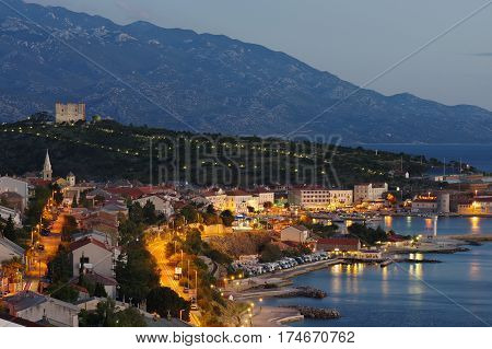 Senj Croatia. A small town in northern Croatia located on the Adriatic coast - night view. The view of the city and harbor from the hill in the northern part of the city. On the hill behind the town is the fortress Nehaj.
