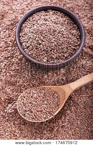 Flax seeds are scattered a solid background in a pile of seeds wooden spoon and plate with flax