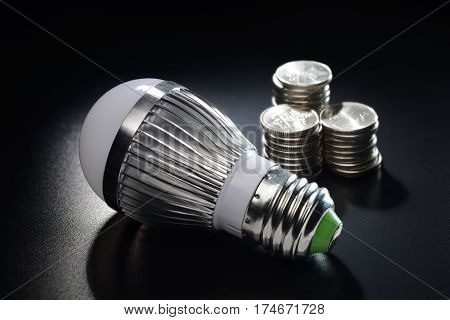 LED energy saving bulb with coins stack on the black grained background