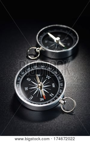 Metal modern compass on black plastic grained background