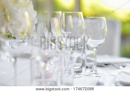 Beautiful table setting with crockery and flowers for a party wedding reception or other festive event. Glassware and cutlery for catered event dinner. poster