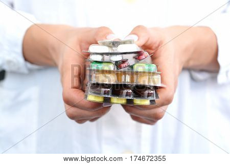 Woman holding a stack of pills blisters in her hands