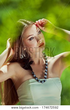 Close-up portrait of a beautiful young woman with your hands near the headlong hair a red lips a thoughtful gaze at the open air in the middle of green blurred leaves at sunny spring day