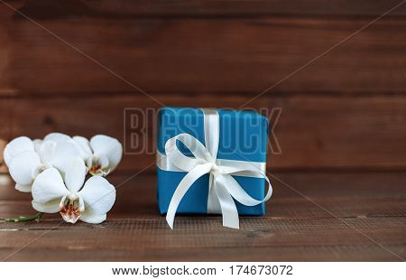 Gift and orchid. The concept of celebration and a welcome card.