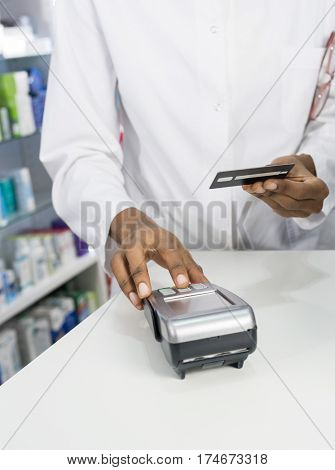 Pharmacist Pressing Buttons Of Card Reader At Counter